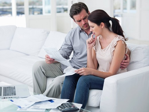 Couple sitting on sofa paying bills together : Stock Photo