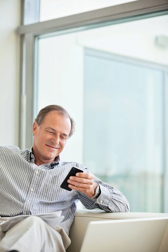 Stock Photo: 1775R-27026 Man text messaging on cell phone