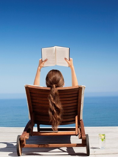 Woman laying in lounge chair reading book : Stock Photo