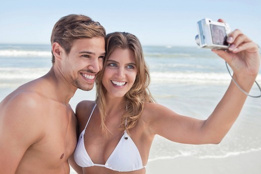Couple taking self_portrait with digital camera on beach : Stock Photo