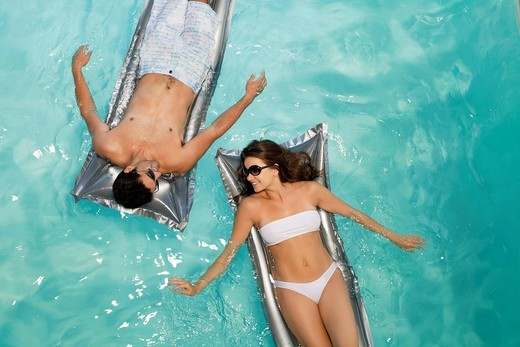 Couple floating in swimming pool together : Stock Photo