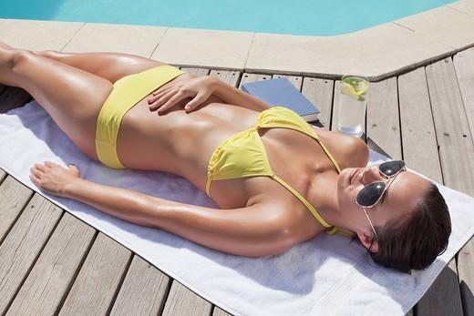 Stock Photo: 1775R-27174 Woman sunbathing near swimming pool