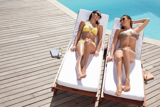 Stock Photo: 1775R-27222 Friends laying on lounge chairs sunbathing near swimming pool