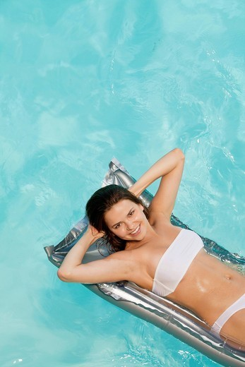 Woman floating in swimming pool sunbathing : Stock Photo
