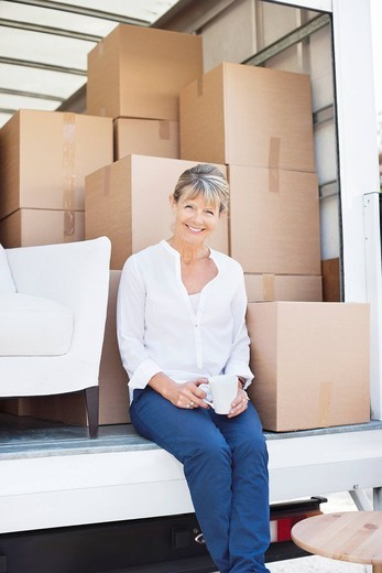Stock Photo: 1775R-27279 Woman drinking coffee on back of moving van