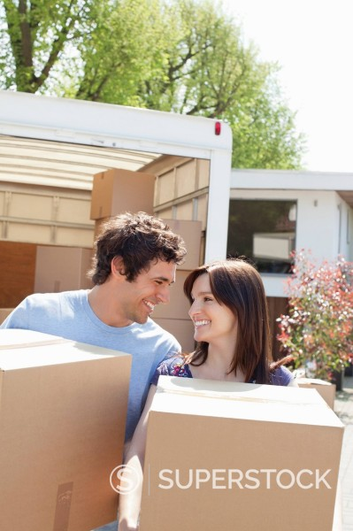 Stock Photo: 1775R-27287 Couple unloading boxes from moving van