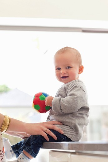 Smiling baby holding ball : Stock Photo