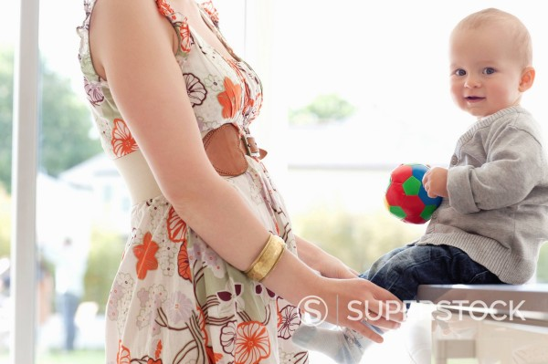 Mother standing with baby holding ball : Stock Photo