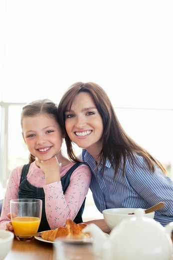 Stock Photo: 1775R-27422 Mother and daughter eating breakfast together