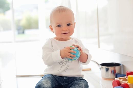 Baby holding toy globe : Stock Photo