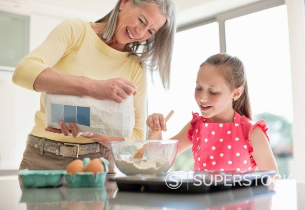 Stock Photo: 1775R-27430 Grandmother and granddaughter baking cupcakes together