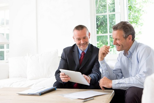 Financial advisor showing digital tablet to customer : Stock Photo