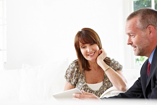 Financial advisor showing digital tablet to client : Stock Photo