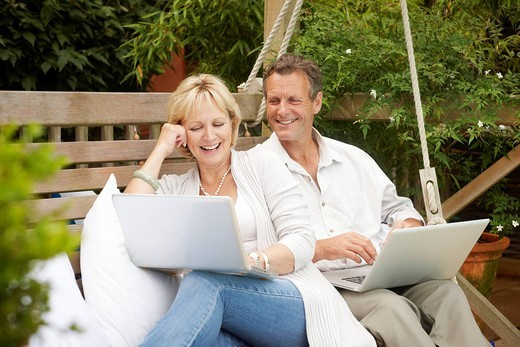 Stock Photo: 1775R-27477 Couple sitting in swing using laptops