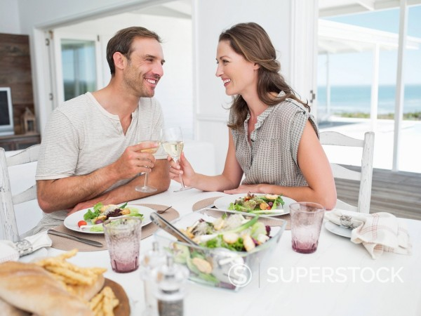 Stock Photo: 1775R-27584 Smiling couple eating lunch and toasting wine glasses at table