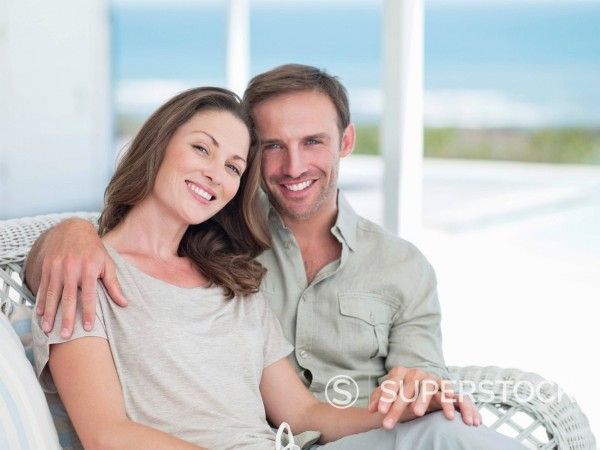 Stock Photo: 1775R-27625 Portrait of smiling couple hugging on patio overlooking ocean