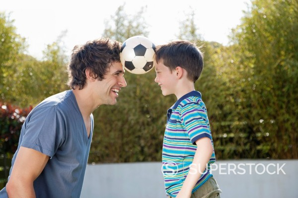 Stock Photo: 1775R-27766 Soccer ball between father and son