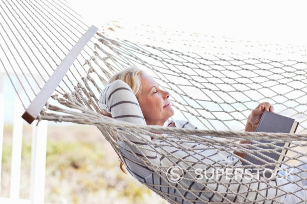 Stock Photo: 1775R-27850 Serene woman with eyes closed laying in hammock with book