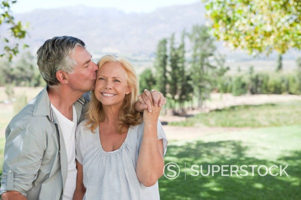 Stock Photo: 1775R-27874 Senior man kissing woman in sunny rural field