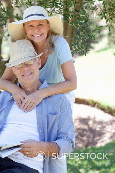 Stock Photo: 1775R-27876 Portrait of smiling senior couple hugging in garden