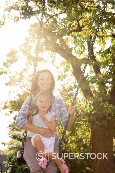 Stock Photo: 1775R-27998 Mother pushing daughter on swing in sunny park