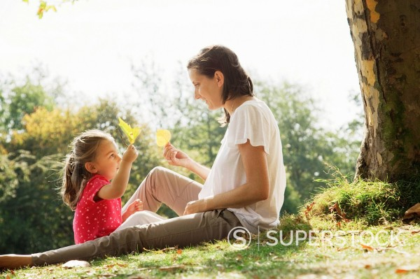 Stock Photo: 1775R-28001 Mother and daughter holding leaves under tree