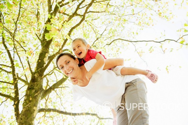 Stock Photo: 1775R-28004 Mother piggybacking daughter under tree