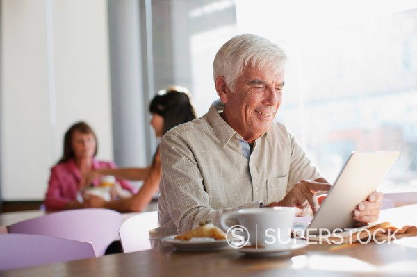 Older man using tablet computer in cafe : Stock Photo