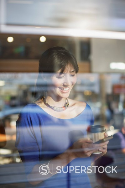 Woman using cell phone in cafe : Stock Photo