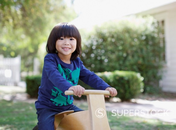Boy riding toy bicycle outdoors : Stock Photo