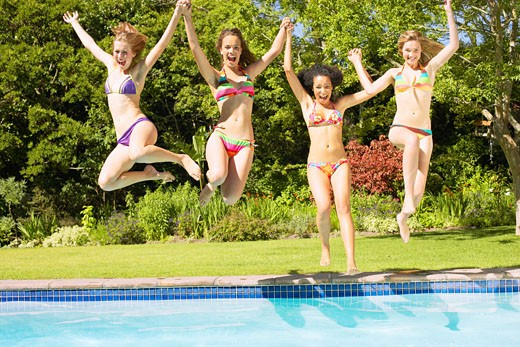 Stock Photo: 1775R-2841 Four teenage girls jumping into pool