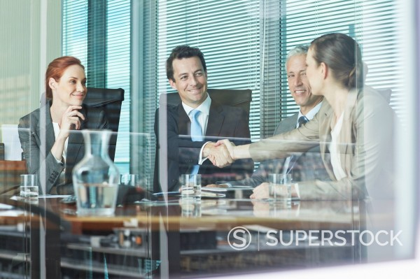 Business people shaking hands at table in conference room : Stock Photo