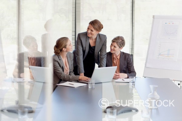 Businesswomen working at laptop in conference room : Stock Photo