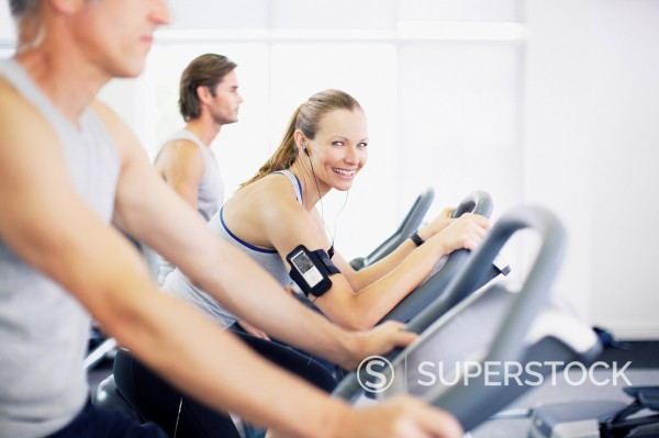 Stock Photo: 1775R-28780 Portrait of smiling woman on exercise bike in gymnasium