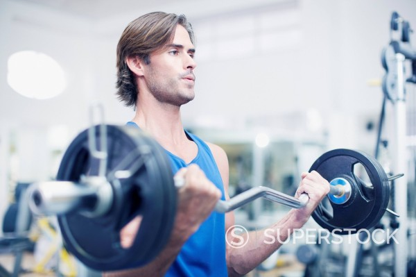Stock Photo: 1775R-28802 Man lifting barbell in gymnasium