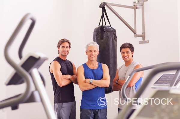 Portrait of smiling men with arms crossed near punching bag : Stock Photo