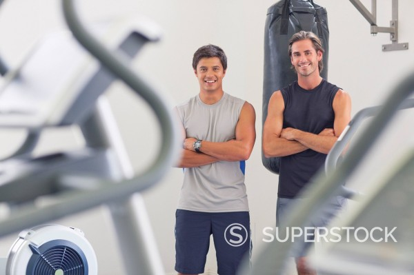 Stock Photo: 1775R-28829 Portrait of smiling men with arms crossed in front of punching bag
