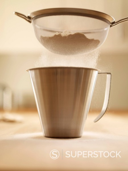 Stock Photo: 1775R-28998 Flour being sifted into measuring cup