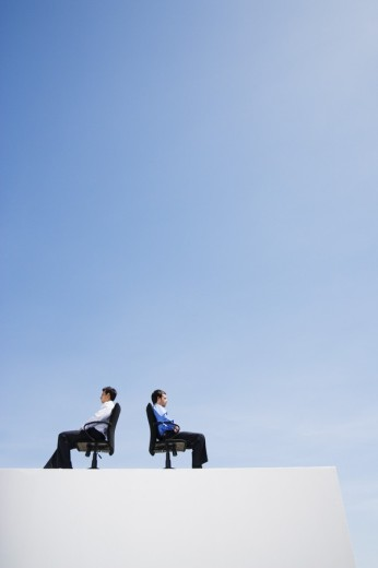 Stock Photo: 1775R-2907 Two businessmen on wall with office chairs back to back