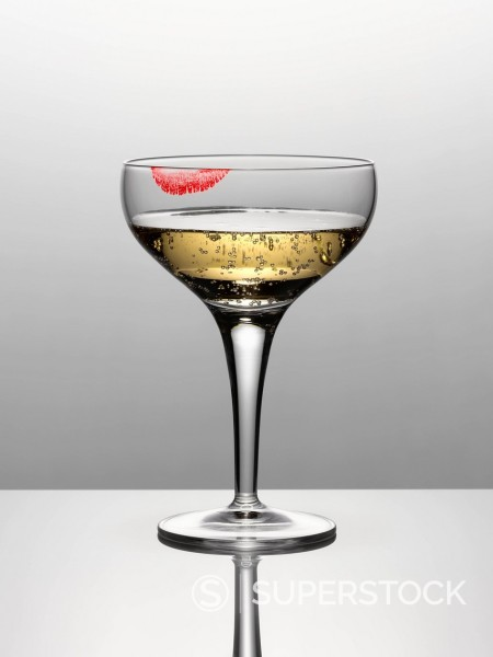 Close up of champagne in glass with lipstick stain : Stock Photo