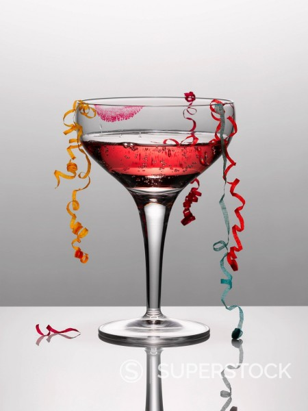 Confetti hanging from glass of pink champagne with lipstick stain : Stock Photo