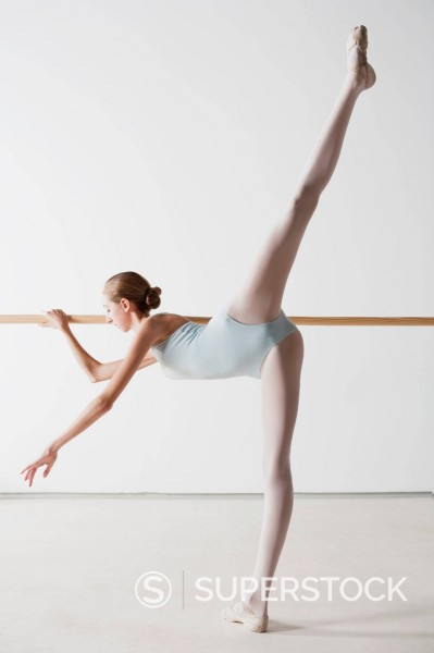 Stock Photo: 1775R-29250 Ballet dancer stretching at barre