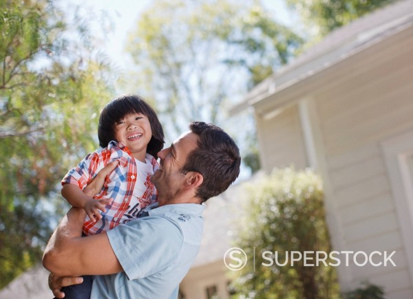 Smiling father holding son outdoors : Stock Photo
