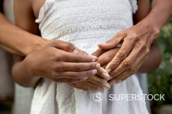 Close up of older woman and granddaughter's hands : Stock Photo