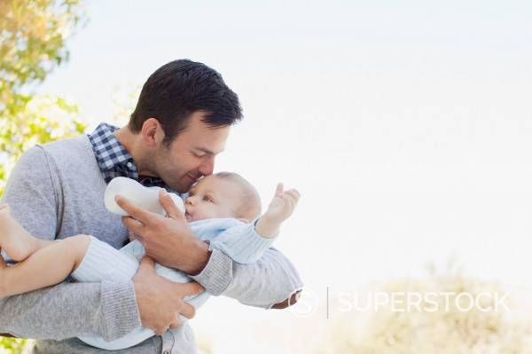 Father bottle feeding baby outdoors : Stock Photo