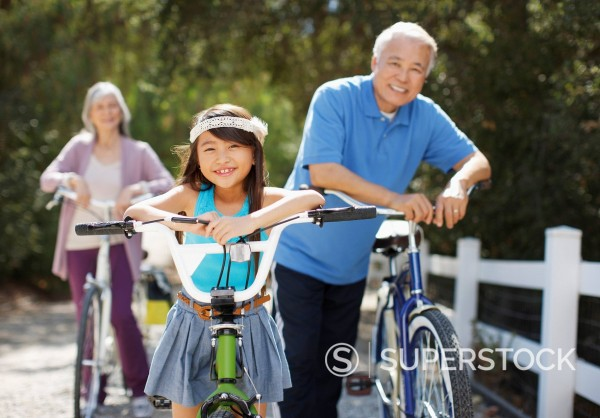 Stock Photo: 1775R-29713 Older couple and granddaughter riding bicycles outdoors