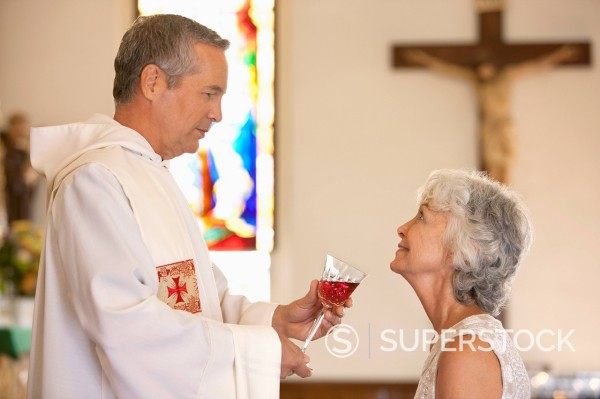 Priest giving communal wine to woman : Stock Photo
