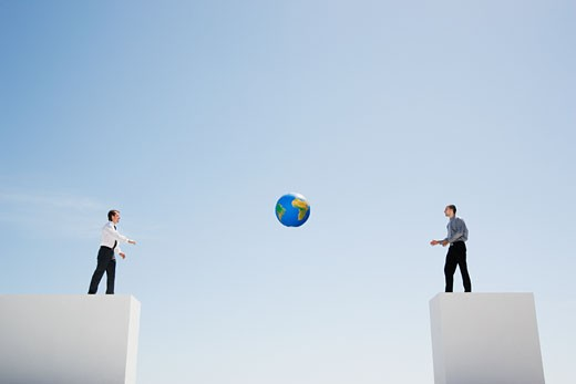 Two businessmen tossing standing on walls with large gap tossing soccer ball : Stock Photo