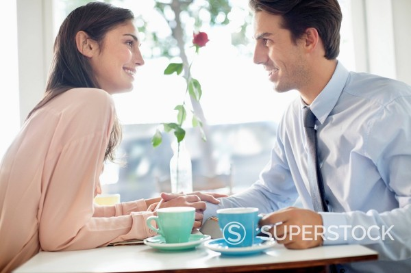 Stock Photo: 1775R-30154 Smiling couple holding hands and drinking coffee in café