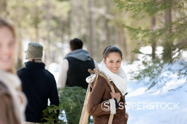 Stock Photo: 1775R-30157 Friends with fresh cut Christmas tree and sled in snowy woods